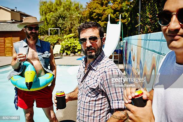 Man drinking beer with friends during pool party