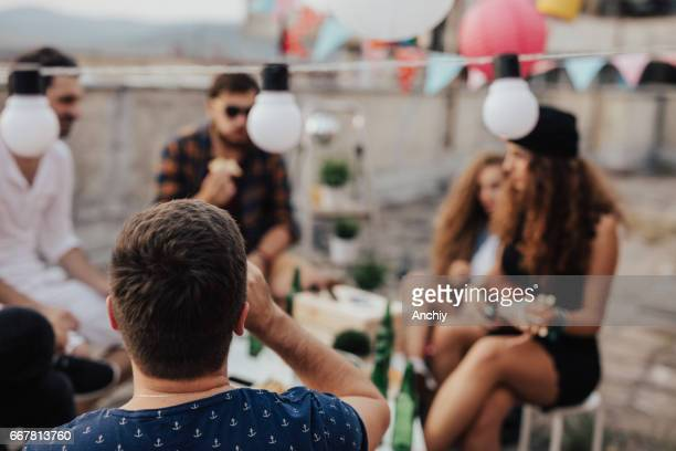 Man drinking beer with his friends on the roof
