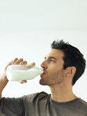 Man drinking bottle of milk, close-up