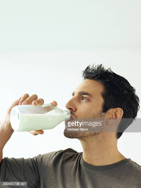Man drinking bottle of milk, close-up