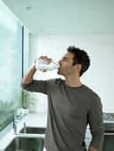 Man drinking bottle of milk in kitchen