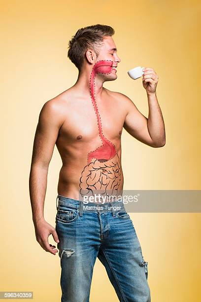 Man drinking coffe with organ displayed on his bod