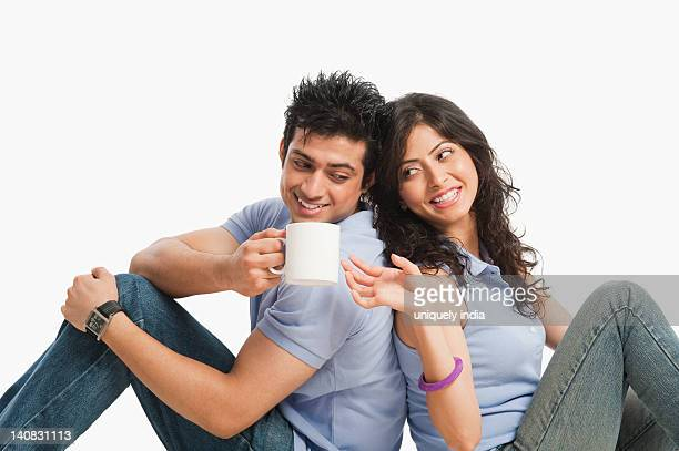 Man drinking coffee and sitting with his girlfriend