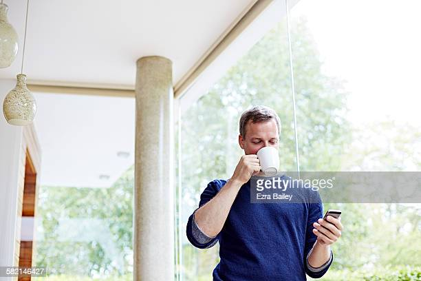 Man drinking coffee checking his phone