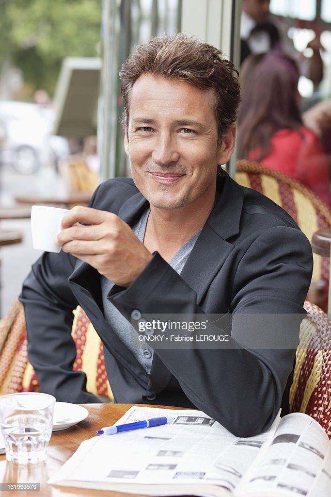 Man drinking coffee in a restaurant, Paris, Ile-de-France, France : Stock Photo