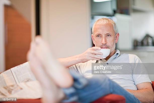 Man drinking coffee in armchair
