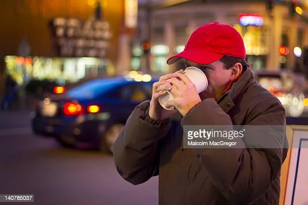 Man drinking coffee on cold night