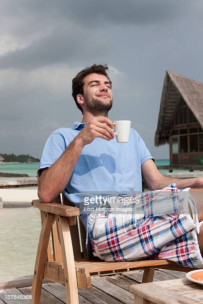 Man drinking coffee on deck at beach