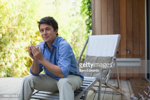 Man drinking coffee on patio : Stock Photo
