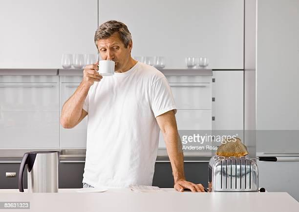 Man drinking coffee while making breakfast