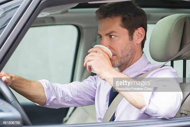 Man drinking coffee whlile driving