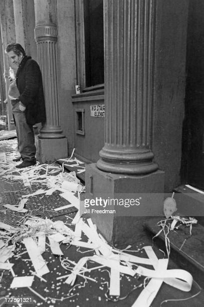 A man drinking from a bottle looks forlornly at the celebratory confetti and cut paper on Prince Street SoHo New York City 1970 A white rat can also...
