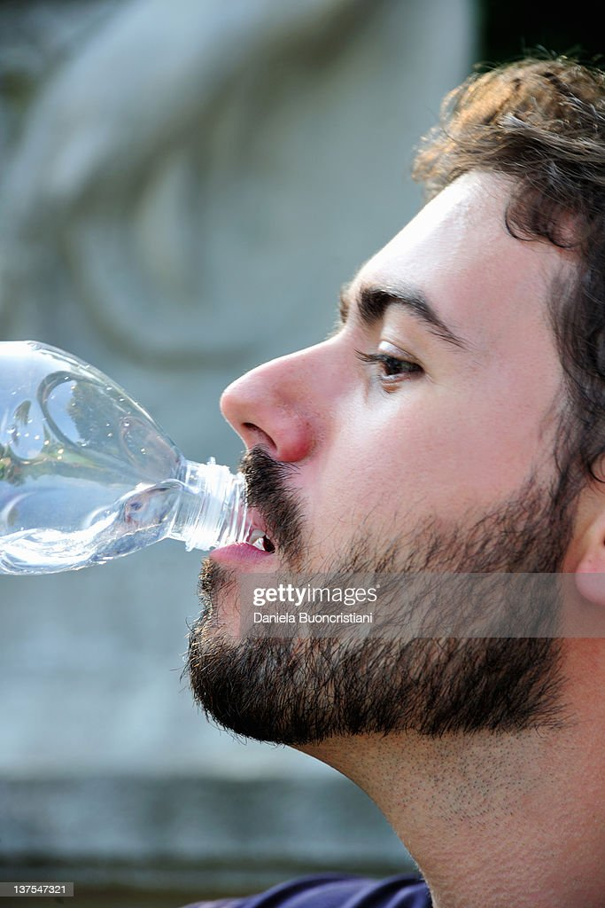Man drinking from water bottle outdoors : Stock Photo