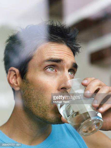 Man drinking glass of water, view through window, close-up