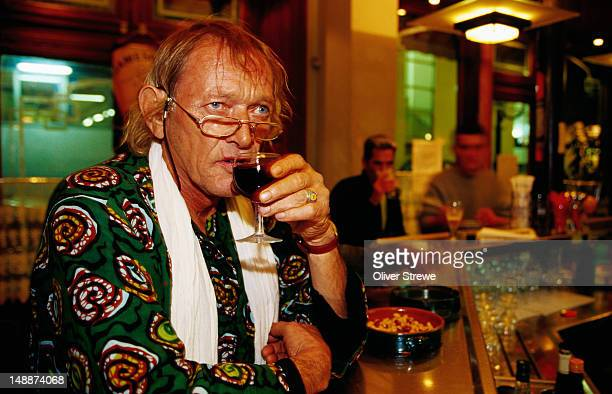 Man drinking red wine in bar.
