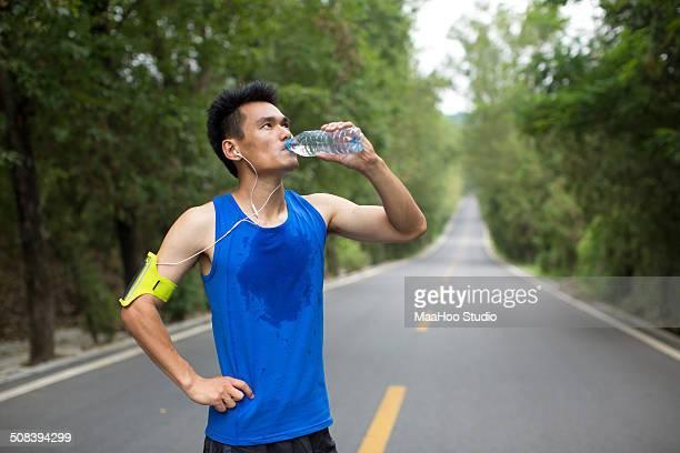 Man drinking water during jogging