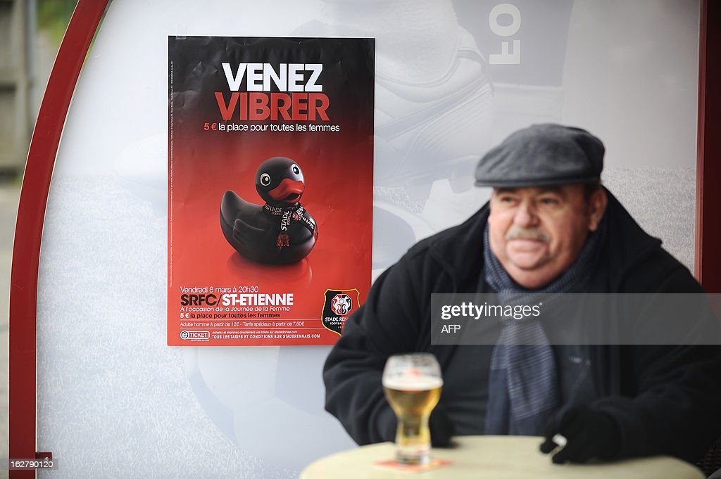 A man drinks a beer infront of an advertising poster of the Stade Rennais football club showing a sex toy and reading 'come to vibrate' on February 27, 2013 in Rennes, western France. Top-flight French football club Rennes risked drawing the wrath of the feminist movement by launching an advertising campaign based at female fans featuring a sex toy with the logo 'Venez vibrer' (come to vibrate). AFP PHOTO / JEAN-SEBASTIEN EVRARD
