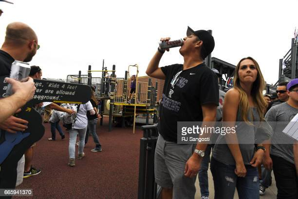 A man drinks a beer outside the kids play area at Coors Field during the Colorado Rockies' home opener on April 7 2017 in Denver Colorado