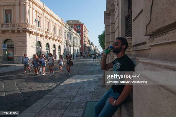 A man drinks a fresh drink to cool off from the heat in the shadow of a tree on August 03 2017 in Reggio Calabria Italy An intense heatwave is...