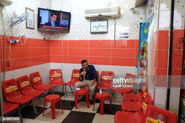 A man drinks a fruit juice while Syrian President Bashar alAssad appears on the TV screen behind him in the city center near the citadel on November...