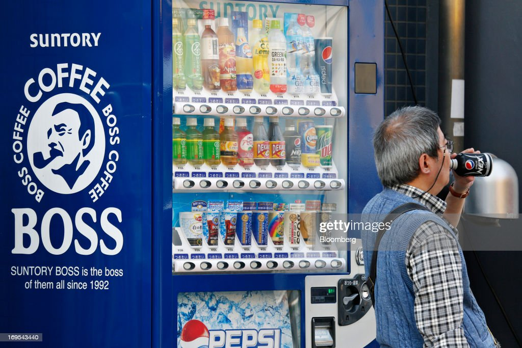 A man drinks a Pepsi Nex beverage developed by Suntory Beverage & Food Ltd. as he passes a Suntory Holdings Ltd. vending machine in Tokyo, Japan, on Sunday, May 26, 2013. Nomura Holdings Inc., Morgan Stanley and JPMorgan Chase & Co. were selected as the lead banks to manage Suntory Beverage & Food Ltd.'s initial public offering, said two people with knowledge of the matter. Photographer: Kiyoshi Ota/Bloomberg via Getty Images