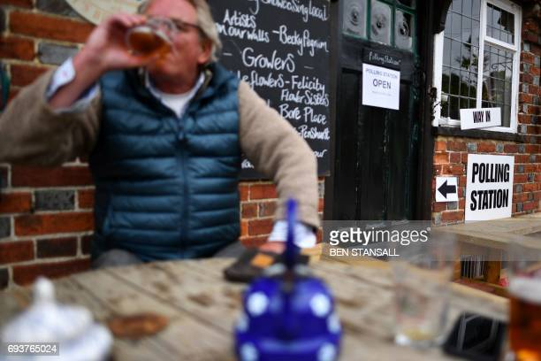 A man drinks beer outside a polling station set up in a pub in Chiddingstone Hoath Kent on June 8 as Britain holds a general election / AFP PHOTO /...