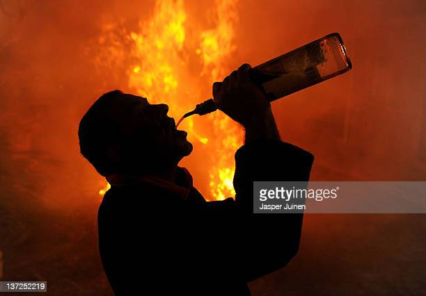 A man drinks liquor from a bottle besides a bonfire on January 16 2012 in the small village of San Bartolome de Pinares Spain In honor of San Anton...