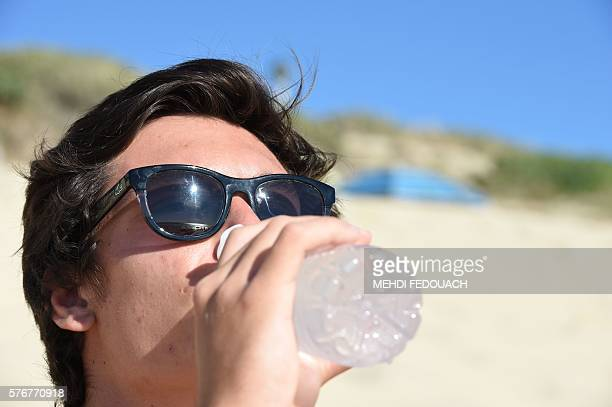 A man drinks on the beach on July 17 2016 in Biscarrosse southwestern France / AFP / Mehdi FEDOUACH