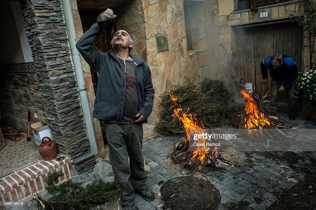 A man drinks wine as he lights a bonfire before the 'Procesion del Humo' (Procession of the Smoke) on November 29, 2015 in Arnedillo, Spain. Villagers of Arnedillo light bonfires of pine and rosemary to honor San Andres every last sunday of November. The roots of this procession are found in 1888 when a outbreak of smallpox devastated the village. The survirvors decided to light a black candle for each of their seven Saints. The candle of San Andres was the last one to go out and villagers decided to name San Andres as Saint Patron of Arnedillo.