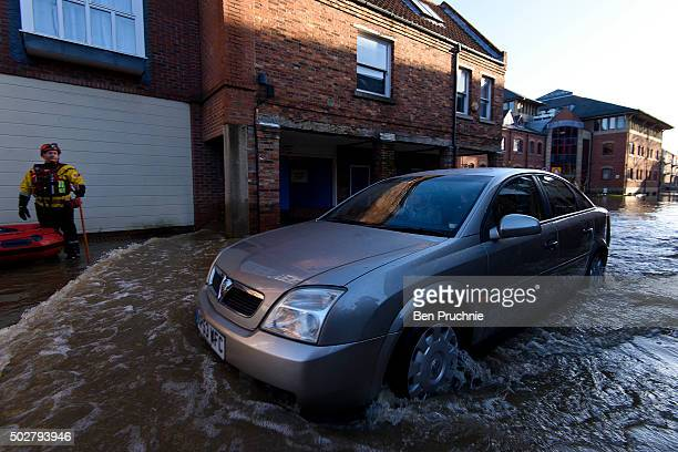 A man drives a car through floodwaters in Skeldergate on December 29 2015 in York England Heavy rain over the Christmas period has caused severe...