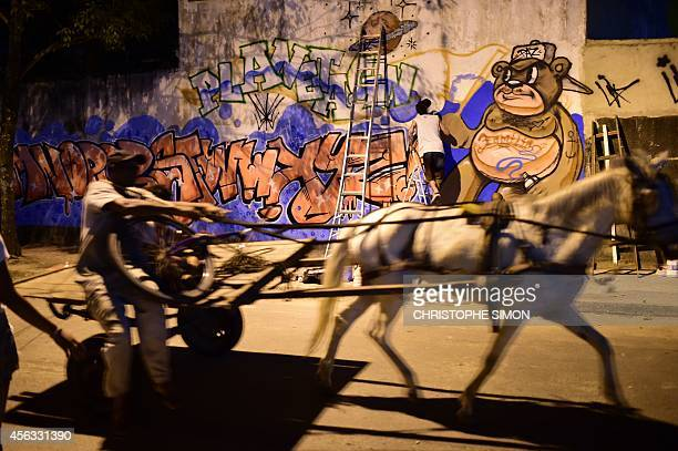 A man drives a cart in front of a graffiti related with the BrazilianFrench 'Planeta Ginga' film and music free festival at the Cidade de Deus...