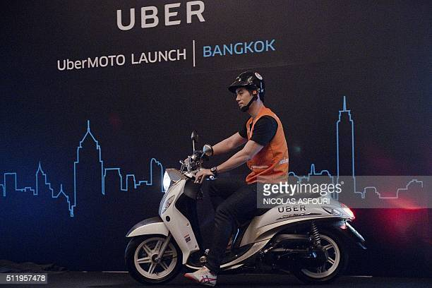 A man drives a motorbike onto a stage during the launch of UberMOTO at a hotel in Bangkok on February 24 2016 Uber offered its first motorbike taxi...