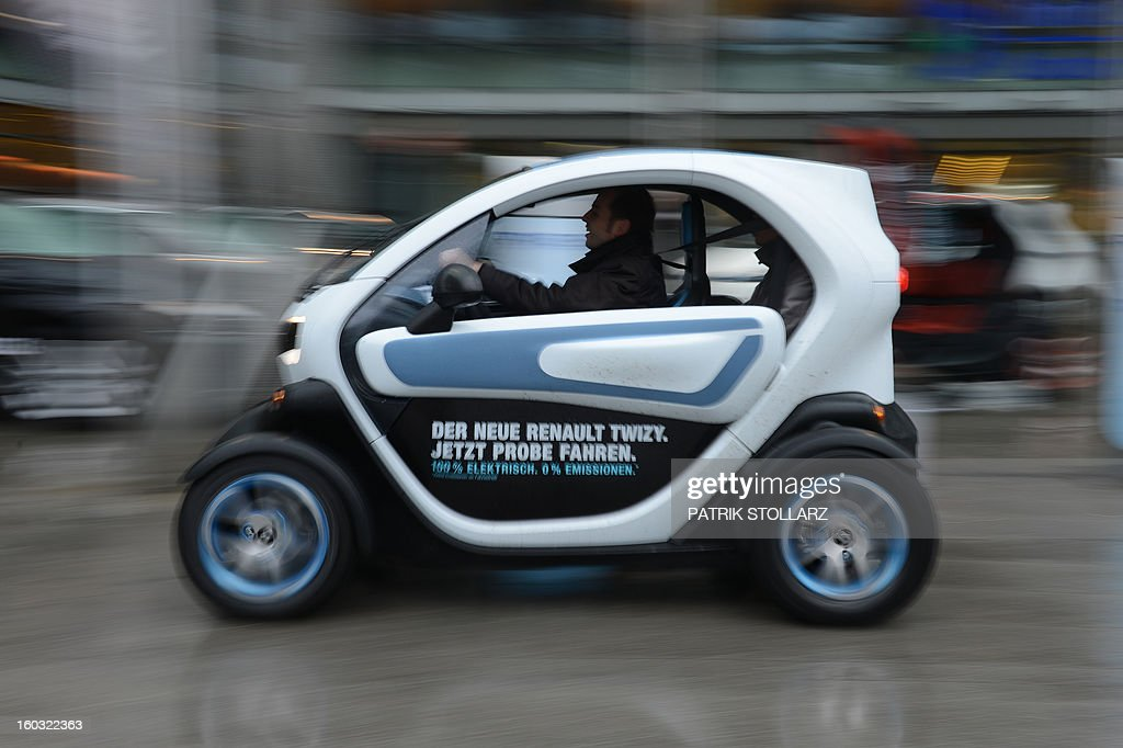 A man drives a Renault Twizy for a test ride during the CAR-Symposium in Bochum, western Germany, on January 29, 2013. Automotive distributers and major car companies discuss about the future of the automotive industries. AFP PHOTO / PATRIK STOLLARZ