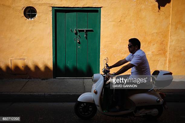 A man drives a scooter through the streets of Cartagena Colombia on January 25 2017 / AFP / David GANNON