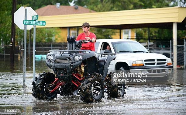 A man drives an offroad vehicle through flooded streets in Slidell northeast of New Orleans on August 30 2012 in Louisiana Tropical Storm Isaac has...