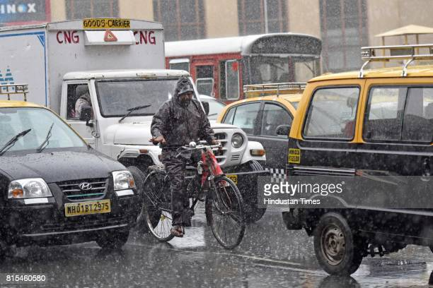 A man drives cycle through the rain near Metro Cinema on July 15 2017 in Mumbai India The IMD issued warnings to the Maharashtra and Gujarat...