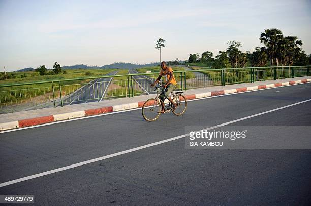 A man drives his bicycle along the new 230 km long AbidjanYamoussoukro highway on May 11 2014 This northern highway inaugurated on December 11 2013...