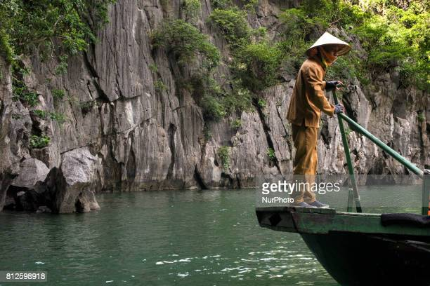 A man drives his boat through Halong Bay considered a UNESCO World Heritage Site The bay of Ha Long is an extension of water of approximately 1500 km...