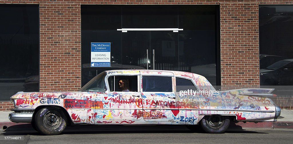 A man drives his hand painted 1959 Cadillac limousine in Hollywood on August 15, 2013 in Los Angeles, California.AFP PHOTO/JOE KLAMAR