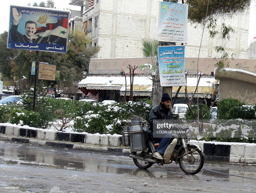 A man drives his motorbike on a road covered with snow on January 10, 2013 in the Syrian capital of Damascus. Snow carpeted Syria's war-torn cities but sparked no let-up in the fighting, instead heaping fresh misery on a civilian population already enduring a chronic shortage of heating fuel and daily power cuts.
