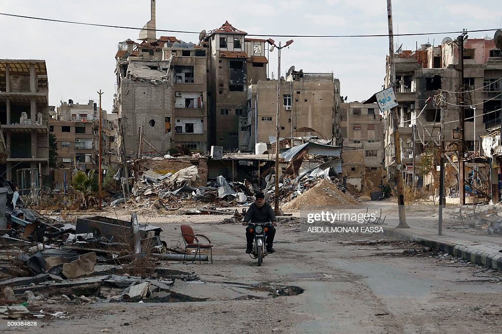 A man drives his motorbike past damaged buildings on February 10, 2016 in Harasta, east of the Syrian capital Damascus. / AFP / ABDULMONAM EASSA