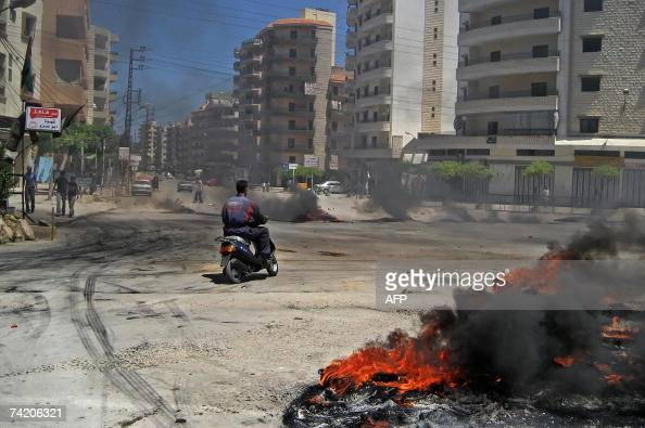 A man drives his motorcycle past burning tires at the entrance of Palestinian refugee camp of Bedawi adjacent to the besieged camp of Naher alBared...