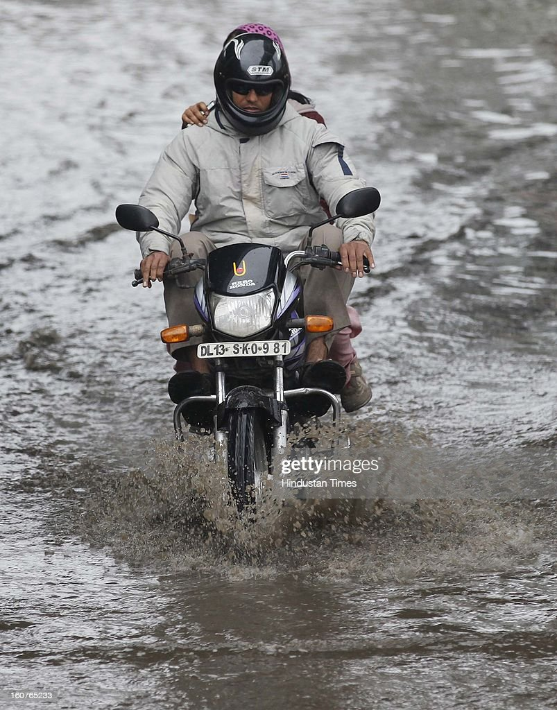 A man drives his vehicle through a water logged road at Akshardham Area on February 5, 2013 in New Delhi, India. The persistent rains since late last night break the seven decade old record for the highest rainfall in a single day in February and triggeredmassive traffic jams due to water-logging across the city.