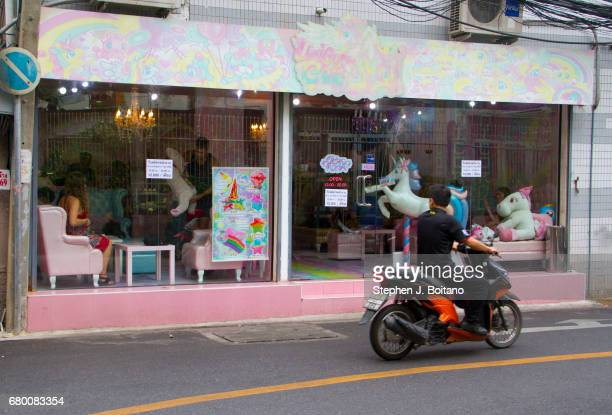 A man drives past the Unicorn Cafe a unicorn and rainbow themed cafe in Bangkok Thailand