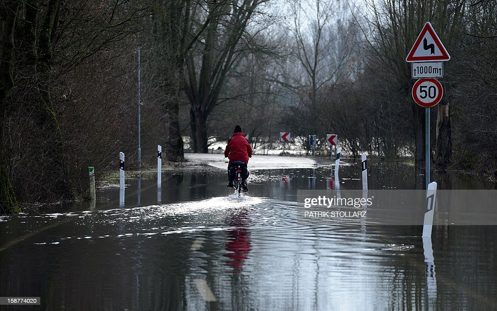 A man drives with his bike through a flooded street near the river Rhine on December 28, 2012 near Duesseldorf, western Germany. AFP PHOTO / PATRIK STOLLARZ