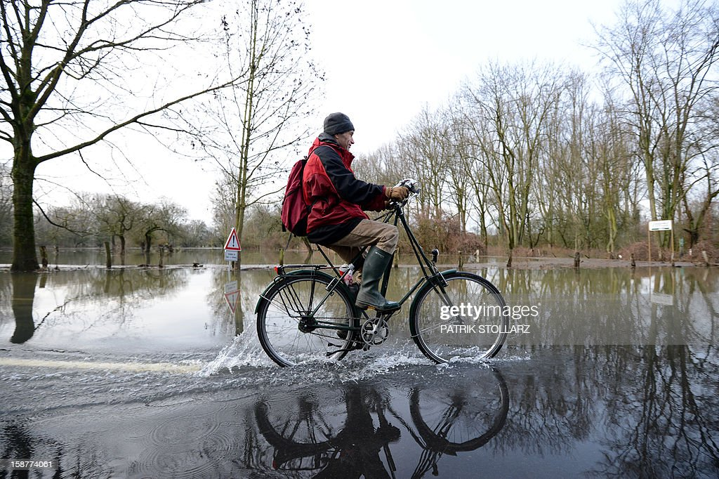 A man drives with his bike through a flooded street near the river Rhine on December 28, 2012 near Duesseldorf, western Germany.