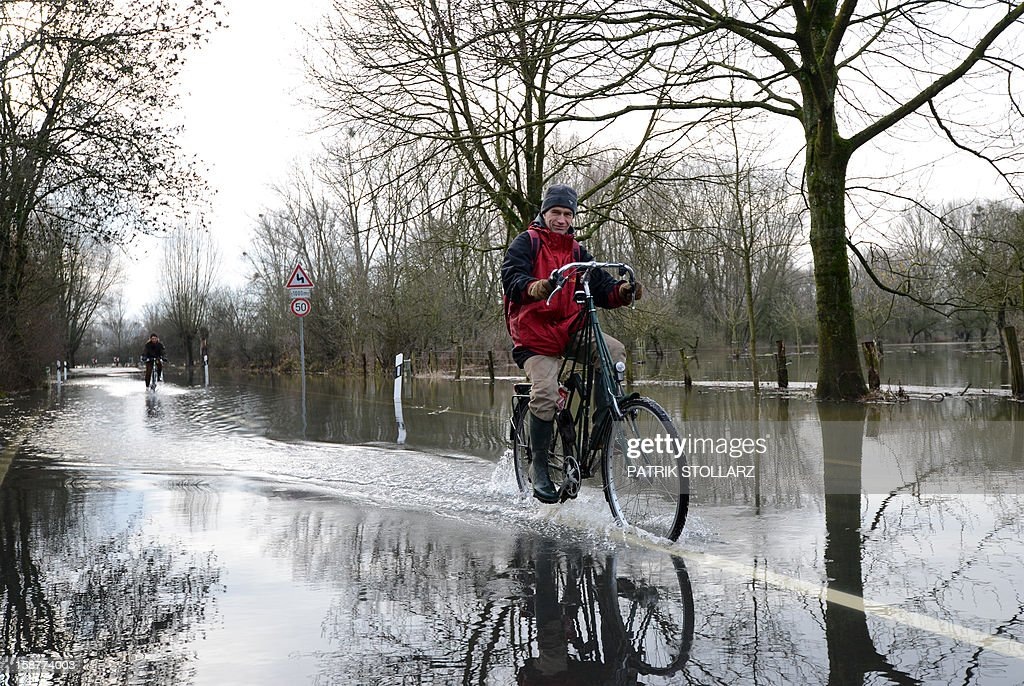 A man drives with his bike through a flooded street on the river Rhine on December 28, 2012 near Duesseldorf, western Germany.