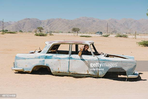 Man driving a car abandoned on the Namib desert, Solitaire, Namibia