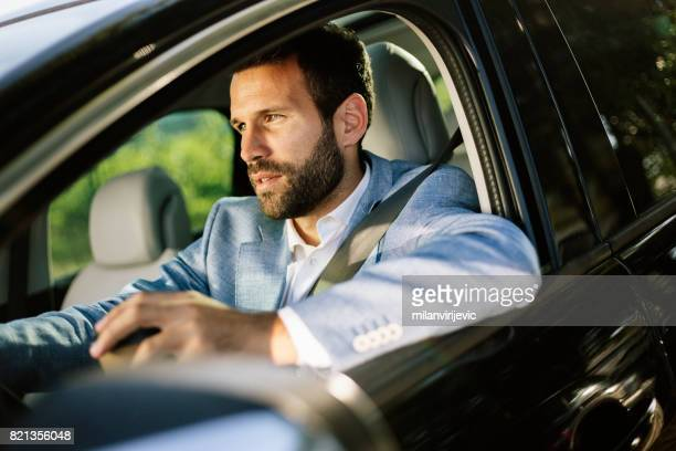 Man driving a car and having coffee cup