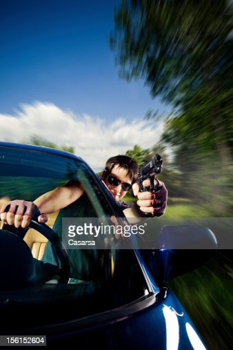 Man driving a car and shooting